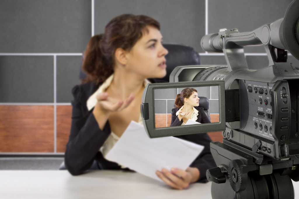 camera view of a female reporter in a news room